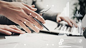Picture of female hands with pen.Businessmans crew working investment project modern office.Using contemporary laptop. Worldwide connection technology icons,stock exchanges graphics interface.