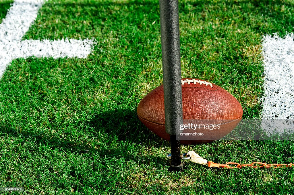 Closeup photo of an American football and first down post