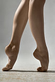 Closeup photo of barefoot legs of the ballerina in the studio on the gray background. She stands on the toes. Closeup. Vertical.