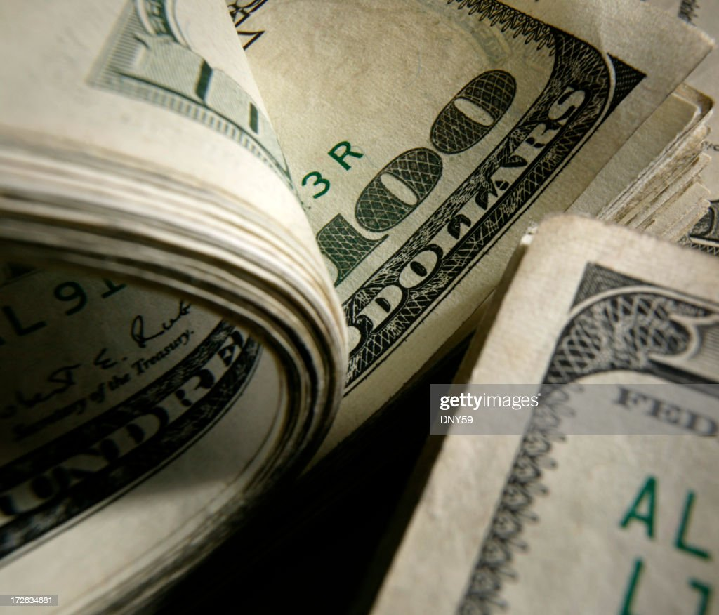 Closeup photo of curled and flat $100 bills : Stock Photo