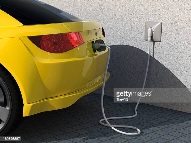 Closeup photo of rear of yellow car plugged into charger