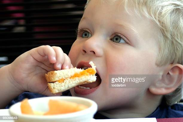 A close-up picture of a young boy eating a sandwich