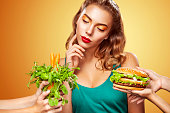 Young sexy woman choosing between burger and vegetarian food