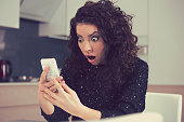 Closeup portrait funny shocked anxious woman looking at phone seeing bad photos message with scared emotion on face