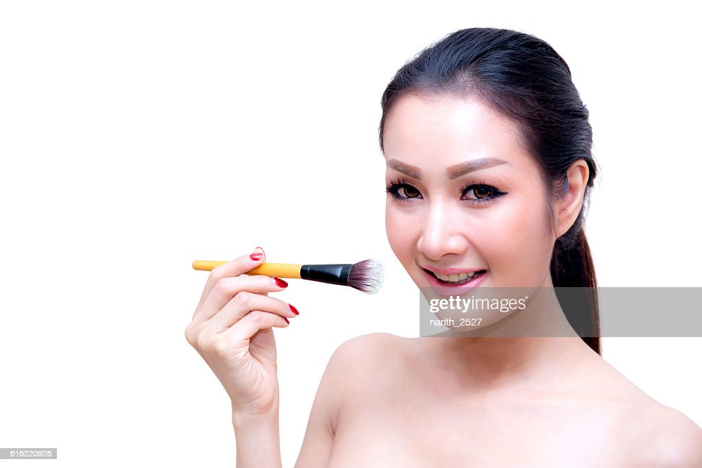 Closeup portrait of a asian woman applying dry cosmetic : ストックフォト