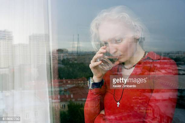Closeup portrait of a blonde woman drinking behind a building window reflecting the city life three quarter view on August 23 2006 in Russia