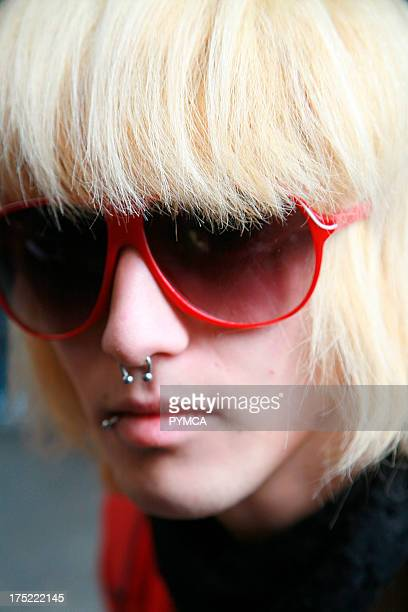 Closeup portrait of a boy with long blond hair red sunglasses and a nose ring Brick Lane UK 2006