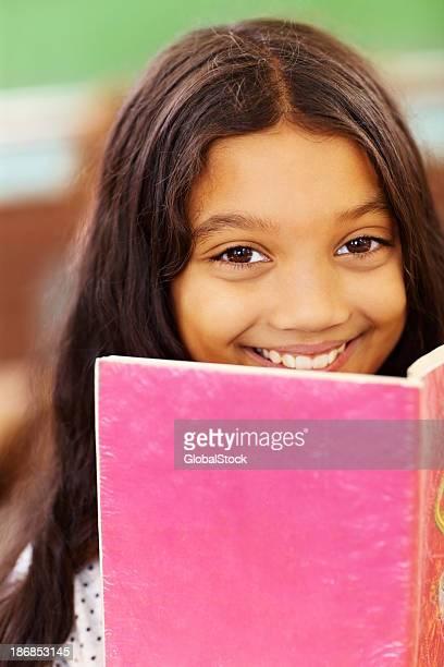 Closeup portrait of a cute school girl reading book