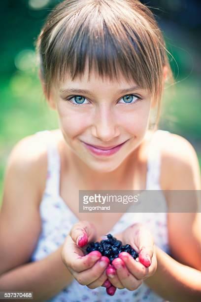 Nahaufnahme Porträt von ein Mädchen halten Handvoll Blaubeeren