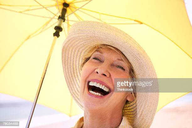 Close-up portrait of a mature woman wearing  a floppy hat, laughing while holding a yellow umbrella