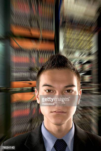 Close-up portrait of a serious young businessman composited with zoom effected computer servers in the background