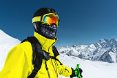 Close-up portrait of a skier in a mask and helmet with a closed face against a background of snow-capped mountains and blue sky.