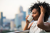 A close-up portrait of a black woman standing on a terrace, drinking coffee. Copy space.