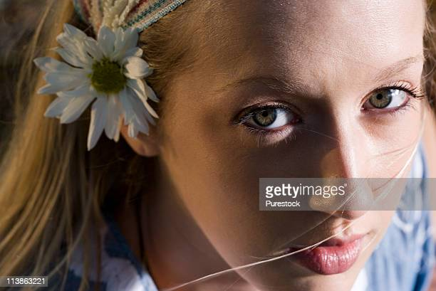 Close-up portrait of a young woman with a flower in her hair