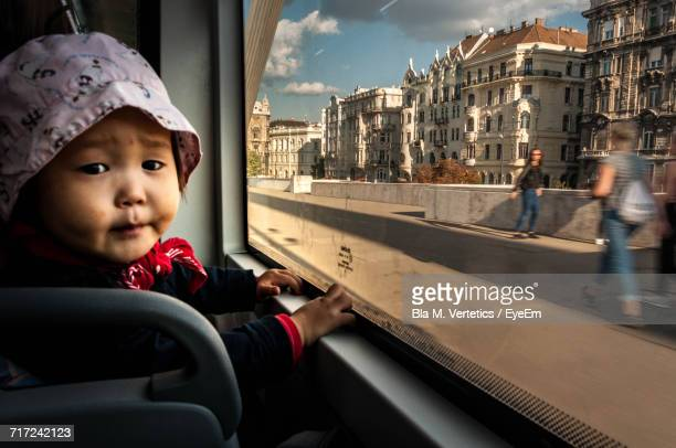 Close-Up Portrait Of Baby Boy Sitting By Window In Bus