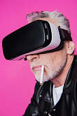 Close-up portrait of bearded senior man with cigarette in mouth using virtual reality headset