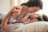 Close-up portrait of beautiful sensual young couple hugging while lying on bed and looking at each other