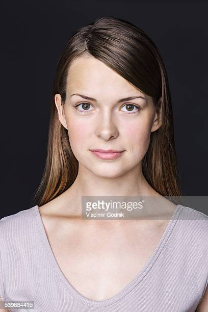 Close-up portrait of beautiful woman against black background