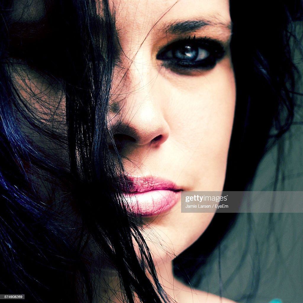 Close-Up Portrait Of Beautiful Woman Covering Her Face With Hair