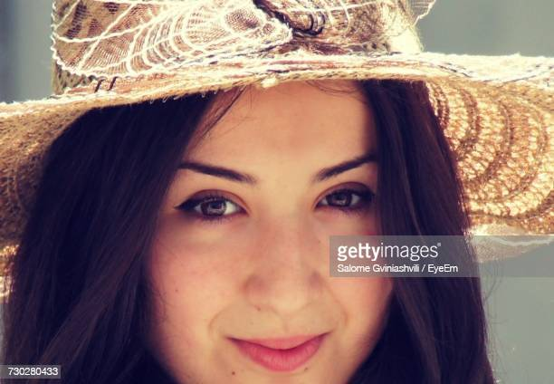 Close-Up Portrait Of Beautiful Woman Wearing Sun Hat On Sunny Day