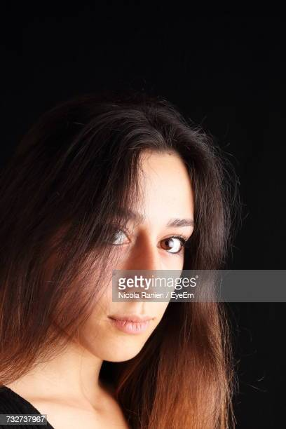 Close-Up Portrait Of Beautiful Woman With Long Hair Against Black Background