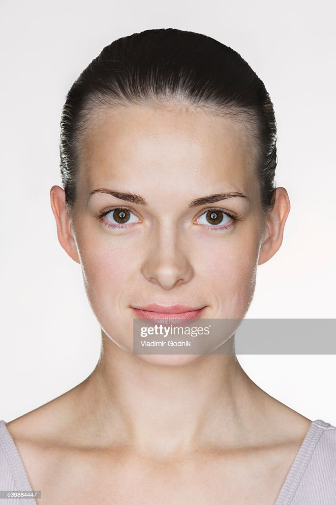 Close-up portrait of beautiful young woman against white background