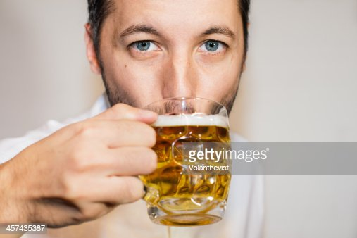 Closeup portrait of blue eyed man drinking beer : Foto de stock