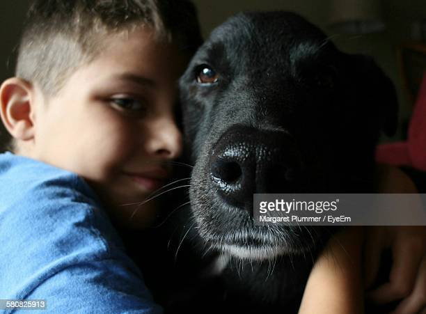 Close-Up Portrait Of Boy Holding Dog At Home