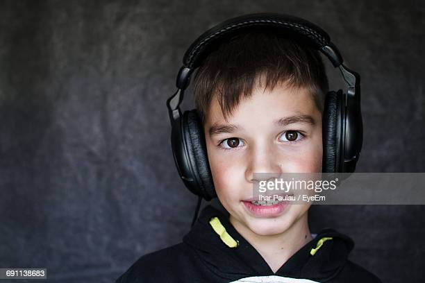 Close-Up Portrait Of Boy Listening Music In Headphones Against Wall