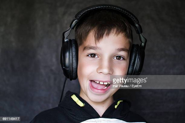 Close-Up Portrait Of Boy Making Face While Listening Music In Headphones Against Wall