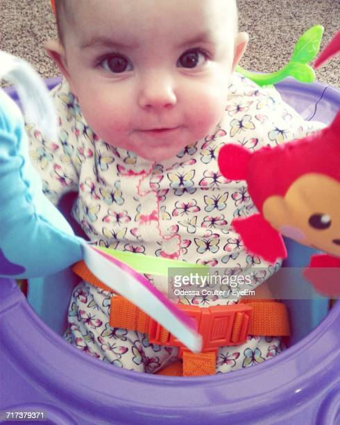 Close-Up Portrait Of Cute Baby Sitting In Walker
