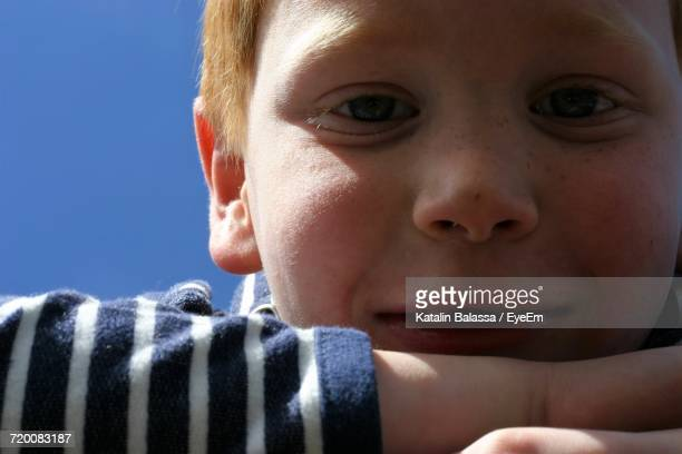 Close-Up Portrait Of Cute Boy Smiling Against Clear Sky