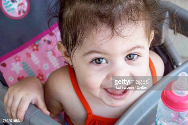 Close-Up Portrait Of Cute Smiling Baby Girl While Sitting In Baby Carriage