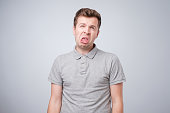 Closeup portrait of funny angry young bully man sticking his tongue out at you camera gesture, isolated on white background. You are disgusting concept
