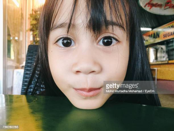 Close-Up Portrait Of Girl At Table