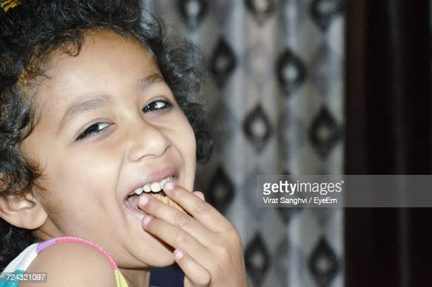 Close-Up Portrait Of Girl Eating At Home