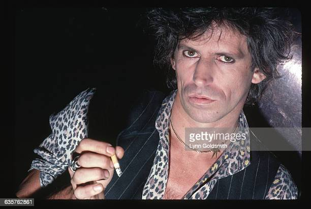 1981 A closeup portrait of guitarist Keith Richards of The Rolling Stones He wears a vest over a leopardprint shirt and holds a cigarette in his hand