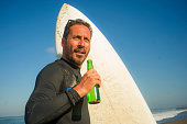 closeup portrait of handsome and attractive surfer man in neoprene swimsuit holding surf board posing cool and happy after surfing enjoying Summer water sport and holidays drinking beer bottle