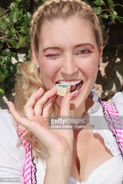 Close-Up Portrait Of Happy Beautiful Woman Eating Chocolate While Winking Eyes