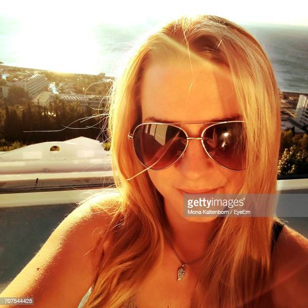 Close-Up Portrait Of Happy Beautiful Woman Standing In Balcony On Sunny Day