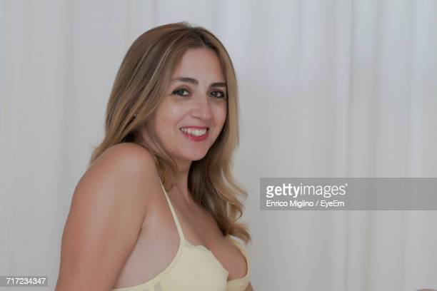 Close-Up Portrait Of Happy Beautiful Woman Wearing Bra By White Curtain