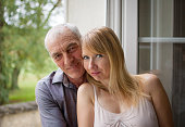 Closeup Portrait of Happy Couple with Age Difference Hugging near the Window in Their Home During Summer Hot Day. Psychology of Relations Concept