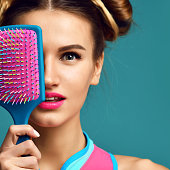 Closeup portrait of happy fashion brunette woman close eyes with colorful pink blue yellow big hair comb brush on modern mint background