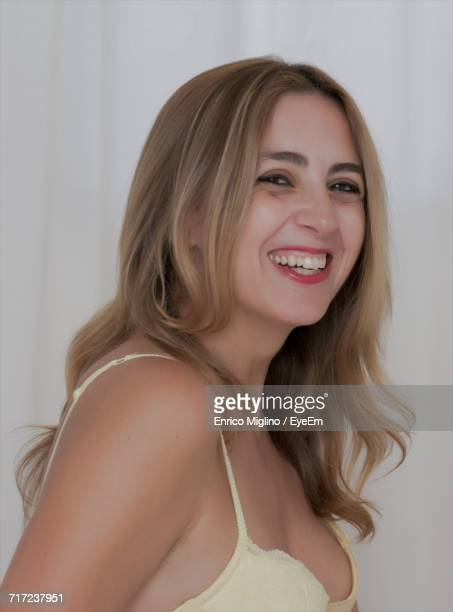 Close-Up Portrait Of Happy Young Woman Wearing Bra By White Curtain