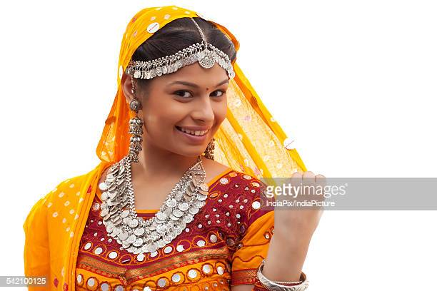 Close-up portrait of happy young woman wearing choli and dupatta over white background