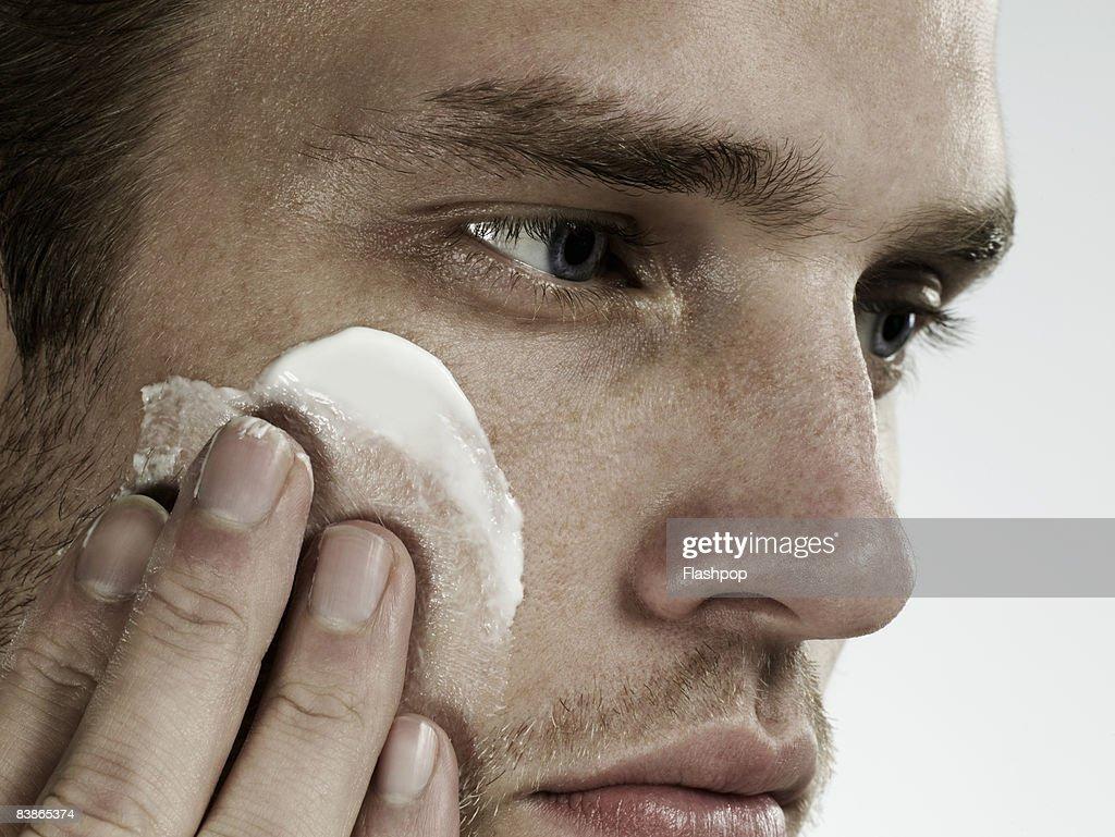 Close-up portrait of man applying moisturizer