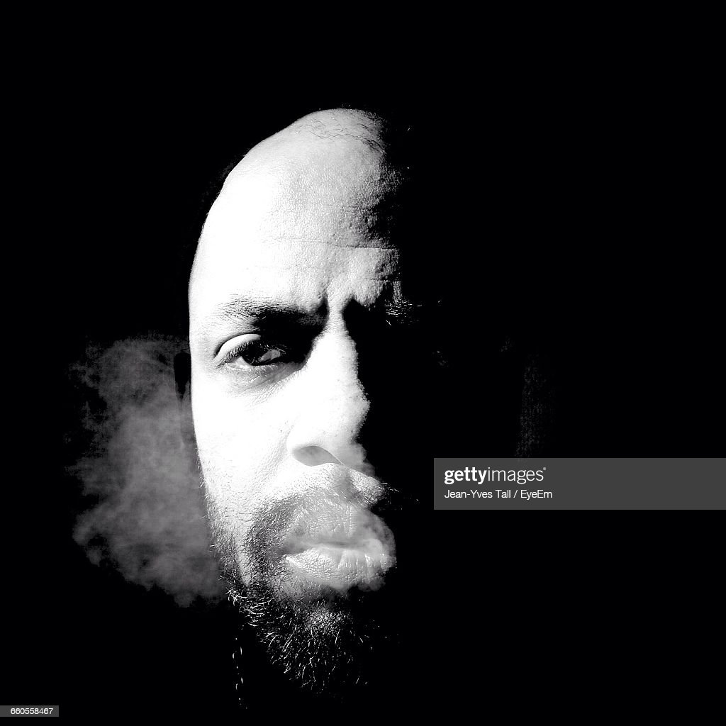 Close-Up Portrait Of Man Smoking Against Black Background