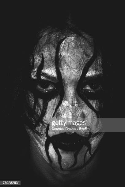 Close-Up Portrait Of Man With Face Paint In Darkroom
