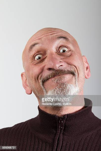 Close-Up Portrait Of Mature Man Making Face Against Gray Background