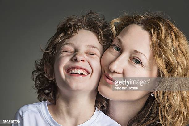 Close-up portrait of mother with cheerful son over gray background